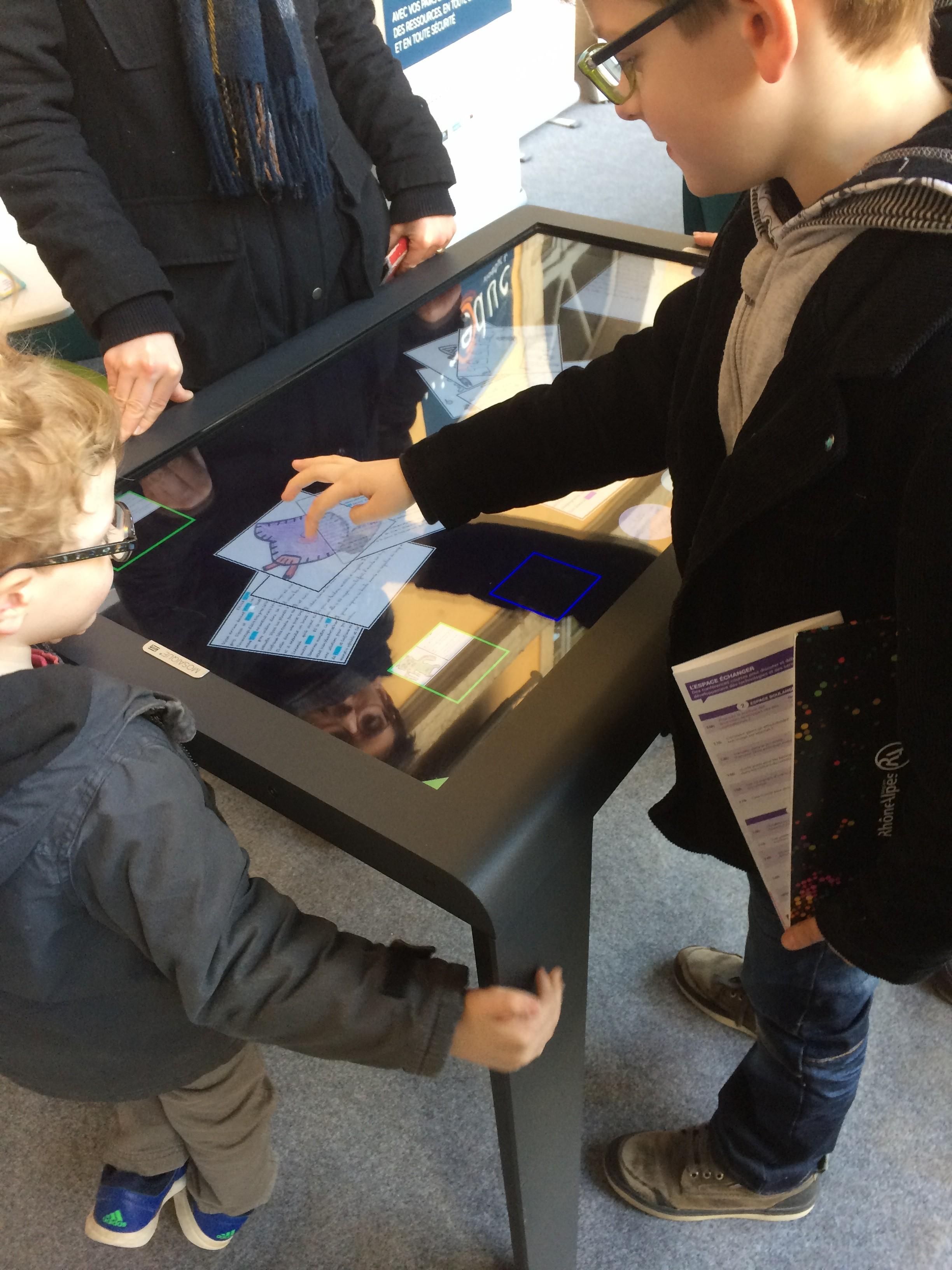 Deux enfants sur une table interactive